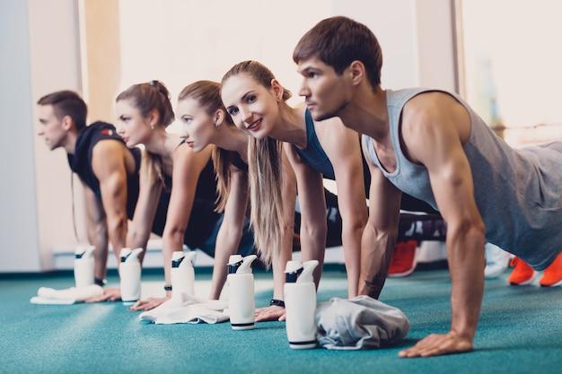 Gruppe männer und frauen führen eine körperliche übung durch. Premium Fotos