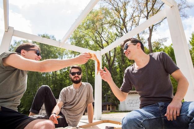 Gruppe männliche freunde, die pizza teilen Kostenlose Fotos