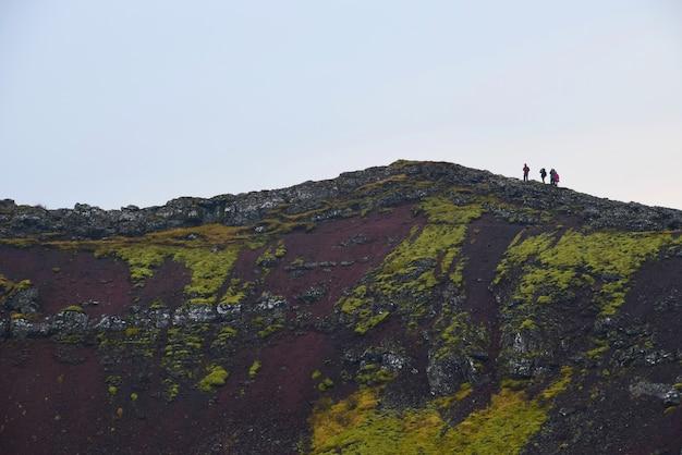 Gruppe reisende, die am rand des kratersees in island klettern. Premium Fotos