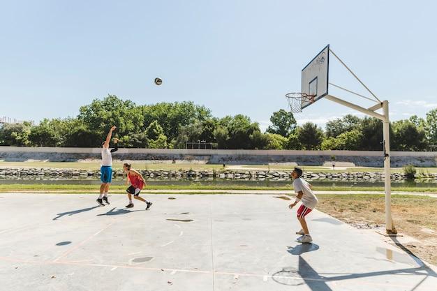 Gruppe spieler, der basketball am gericht draußen spielt Kostenlose Fotos