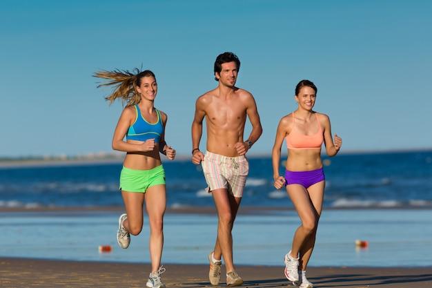 Gruppe sportleute - mann und frauen - rüttelnd auf dem strand Premium Fotos