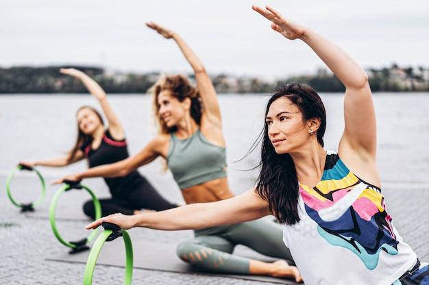 Gruppe sportlicher frauen, die dehnübungen mit einem speziellen sportkreis auf der straße nahe dem wasser tun. Premium Fotos