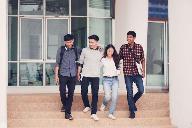 Gruppe studenten, die draußen zusammen in campus gehen Premium Fotos