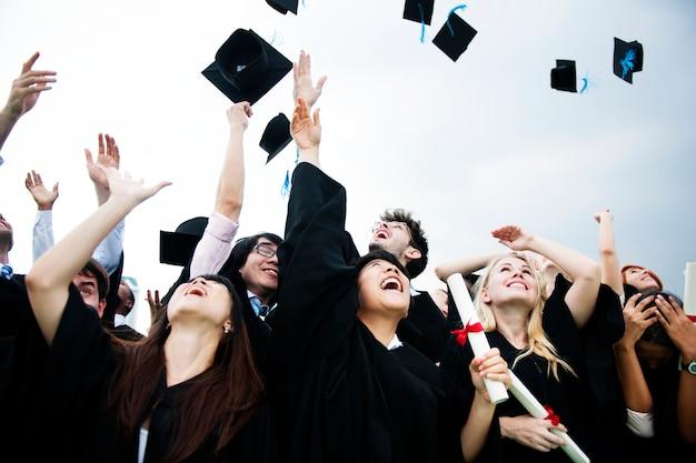 Gruppe verschiedene absolventen, die kappen oben in den himmel werfen Kostenlose Fotos