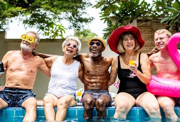 Gruppe verschiedene ältere erwachsene, die durch das pool genießt sommer zusammen sitzen Premium Fotos