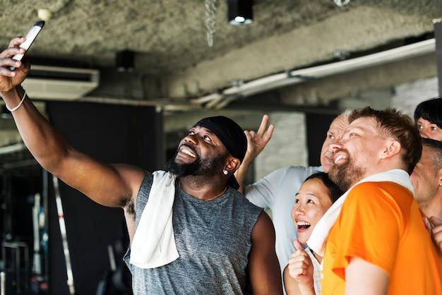 Gruppe verschiedene freunde, die zusammen selfie an der turnhalle nehmen Premium Fotos