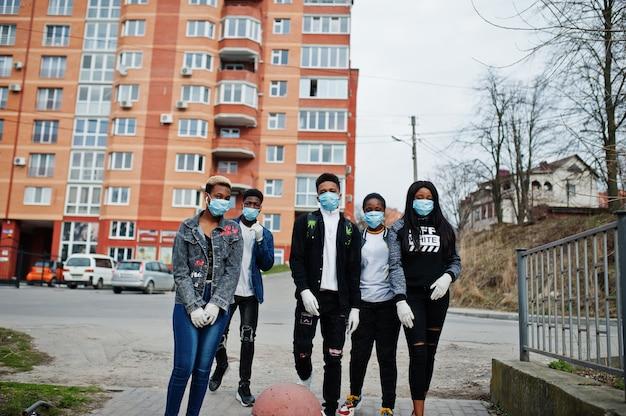 Gruppe von afrikanischen teenagerfreunden gegen leere straße mit gebäude, das medizinische masken trägt, schützen vor infektionen und krankheiten coronavirus-virus-quarantäne. Premium Fotos