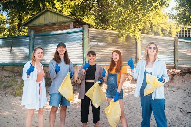 Gruppe von aktivistenfreunden, die plastikmüll am strand sammeln. jungs zeigen daumen hoch. Kostenlose Fotos