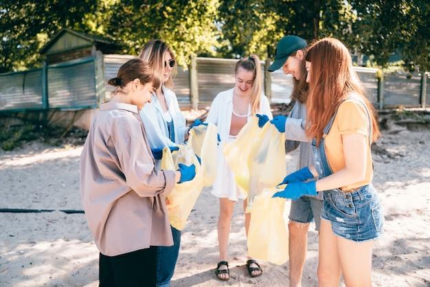 Gruppe von aktivistenfreunden, die plastikmüll am strand sammeln. umweltschutz. Kostenlose Fotos