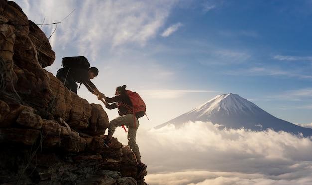 Gruppe von asien-wandern helfen sich schattenbild in den bergen mit sonnenlicht. Premium Fotos