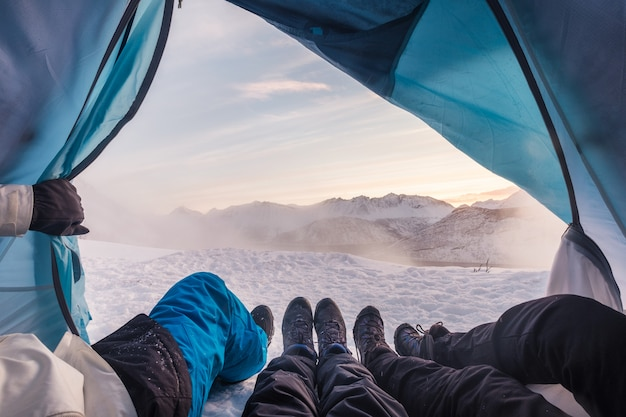 Gruppe von bergsteigern sind in einem zelt mit blick auf schneesturm am berg geöffnet Premium Fotos