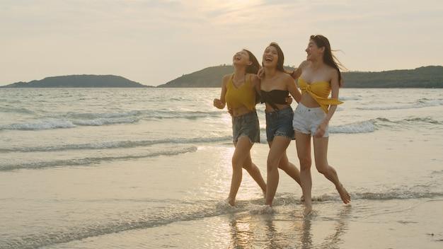 Gruppe von drei asiatischen jungen frauen, die auf strand laufen Kostenlose Fotos