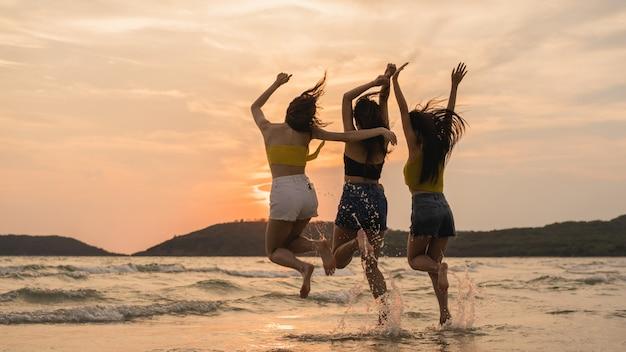 Gruppe von drei asiatischen jungen frauen, die auf strand springen Kostenlose Fotos