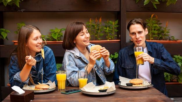 Gruppe von drei freunden, die burger essen Kostenlose Fotos