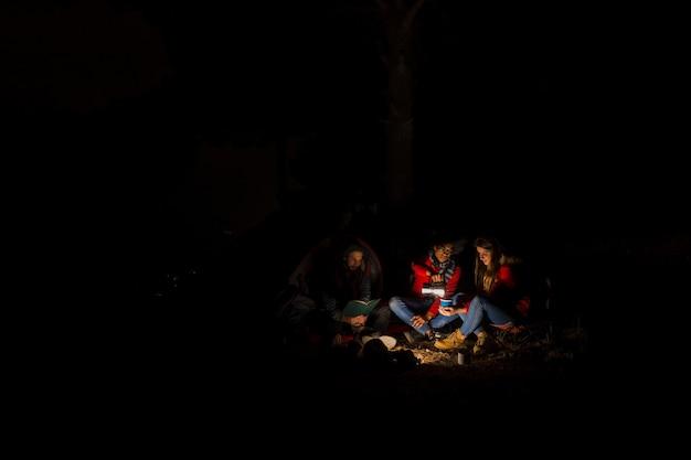 Gruppe von drei freunden, die nachts kampieren Kostenlose Fotos