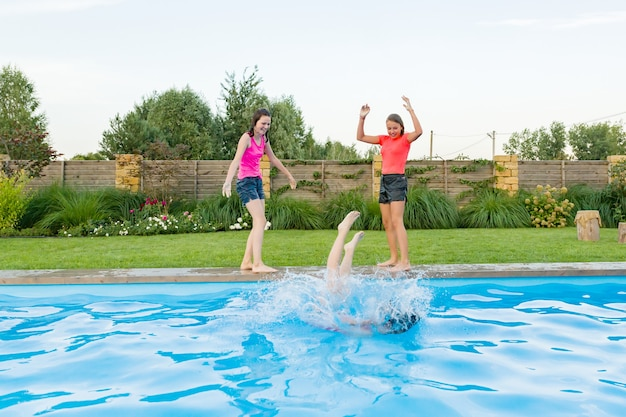 Gruppe von drei jugendlichen freunden, die spaß im schwimmbad haben Premium Fotos
