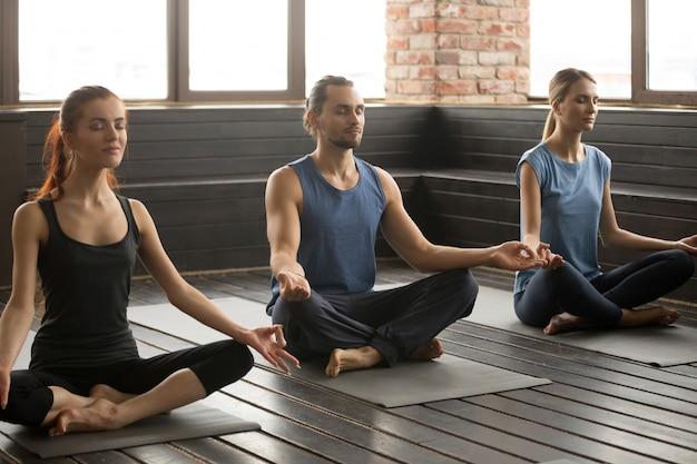Gruppe von drei jungen sportlichen leuten, die in sukhasana sitzen, werfen auf Kostenlose Fotos