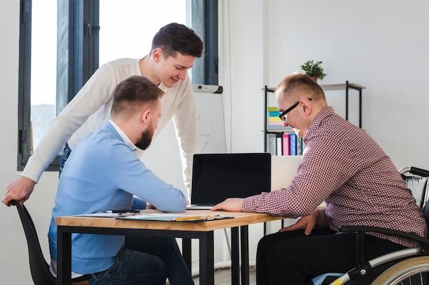 Gruppe von erwachsenen männern, die zusammen im büro arbeiten Kostenlose Fotos