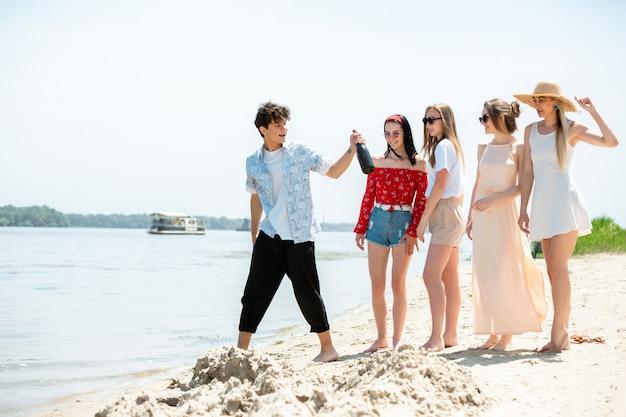 Gruppe von freunden, die am strand feiern Kostenlose Fotos