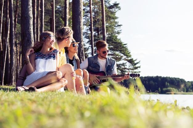 Gruppe von freunden, die bei sonnenuntergang feiern und musik hören. Premium Fotos