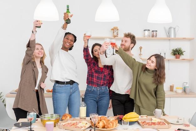 Gruppe von freunden, die beim essen rösten Kostenlose Fotos
