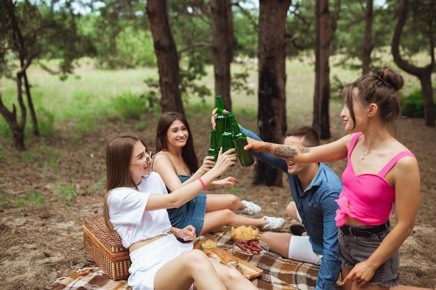 Gruppe von freunden, die bierflaschen während des picknicks im sommerwald klirren Kostenlose Fotos