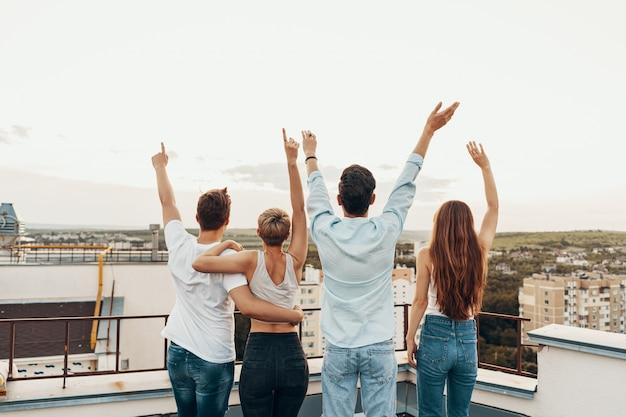 Gruppe von freunden, die draußen am dach genießen Kostenlose Fotos