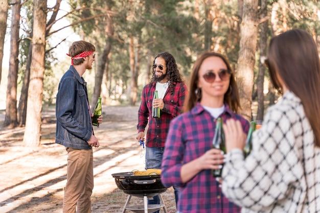 Gruppe von freunden, die einen grill mit bieren haben Kostenlose Fotos
