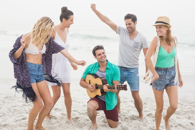 Gruppe von freunden, die gitarre spielen und tanzen Premium Fotos