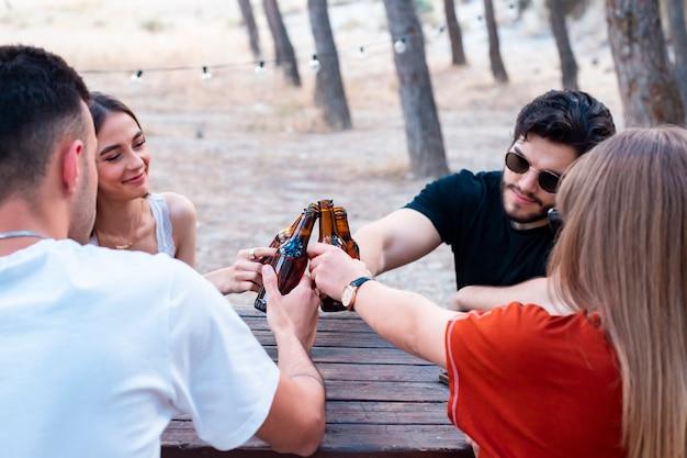 Gruppe von freunden, die mit bieren an einem picknickplatz rösten Premium Fotos