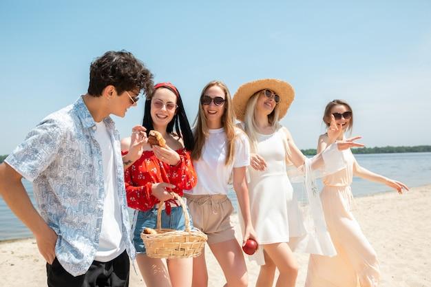Gruppe von freunden, die spaß am strand im sonnigen sommertag haben Kostenlose Fotos