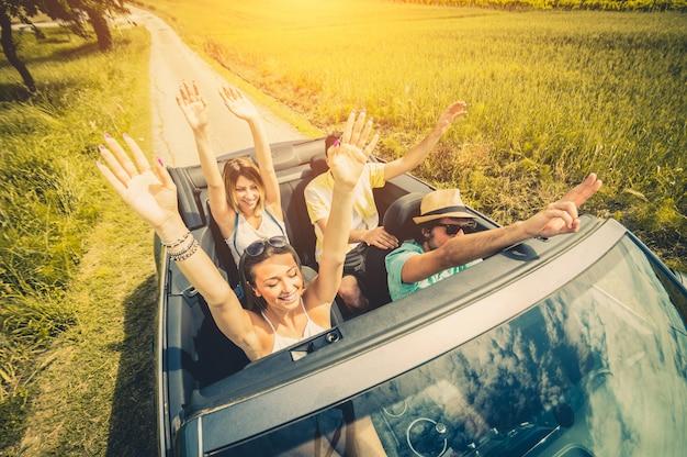Gruppe von freunden, die spaß an der autofahrt durch europa haben. freunde in den ferien fahren auf der straße Premium Fotos