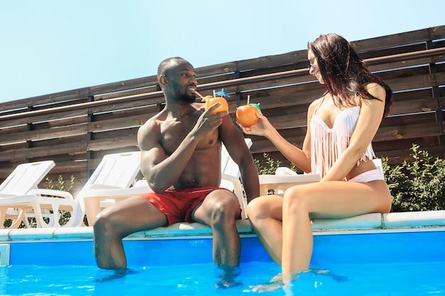 Gruppe von freunden, die während der sommerferien in einem schwimmbad spielen und sich entspannen Kostenlose Fotos