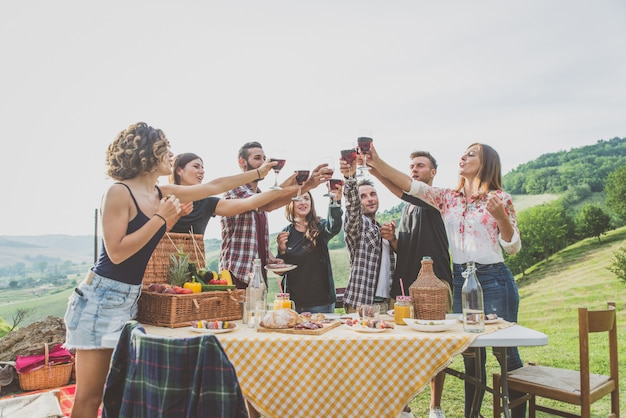 Gruppe von freunden, die zeit damit verbringen, ein picknick und einen grill zu machen Premium Fotos