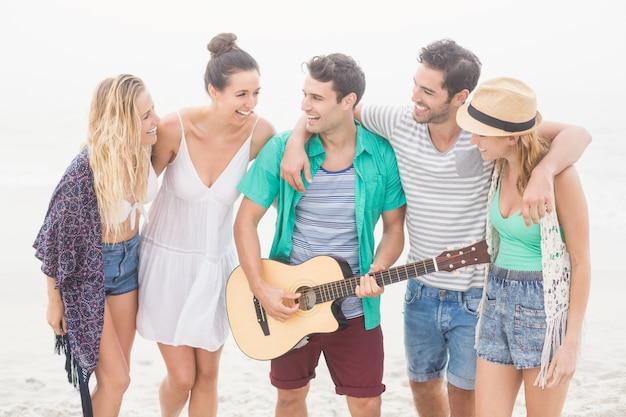 Gruppe von freunden stehen am strand mit einer gitarre Premium Fotos