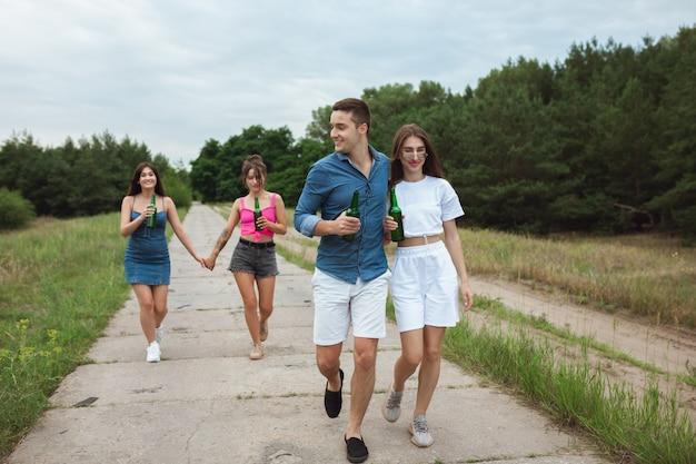 Gruppe von freunden während des picknicks im sommerwald Kostenlose Fotos