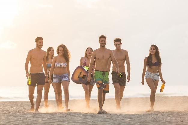 Gruppe von freunden zu fuß am strand bei sonnenuntergang. Premium Fotos