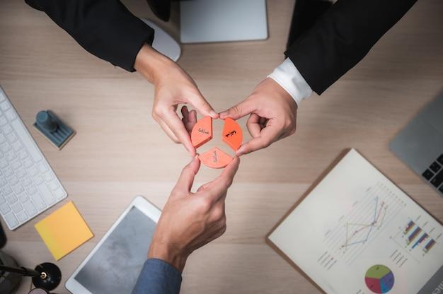 Gruppe von geschäftsleuten, die puzzles zusammenstellen und teamunterstützungs- und hilfekonzept darstellen Premium Fotos