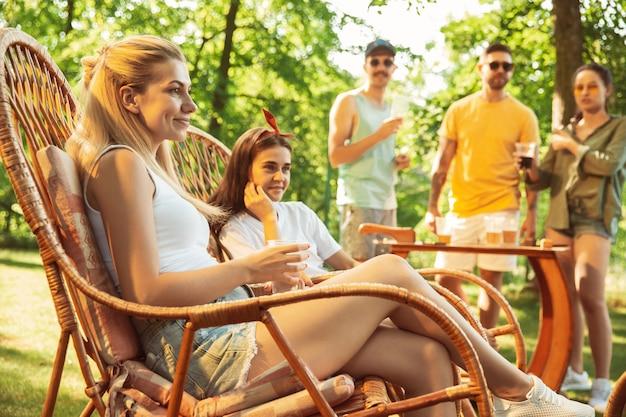 Gruppe von glücklichen freunden, die bier und grillparty am sonnigen tag haben. zusammen im freien in einer waldlichtung oder im hinterhof ausruhen Kostenlose Fotos
