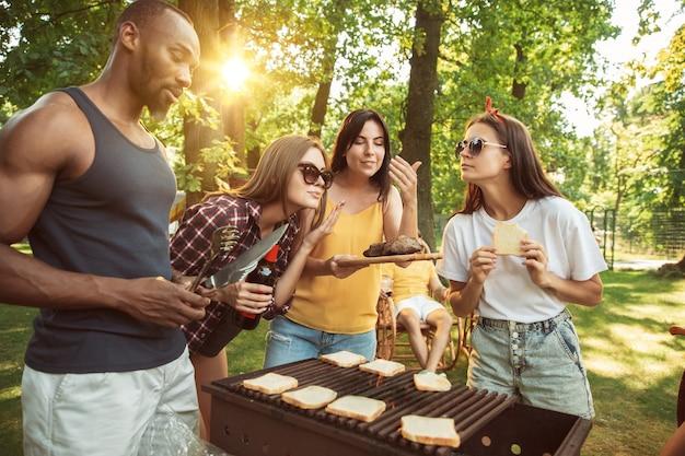 Gruppe von glücklichen freunden, die bier und grillparty am sonnigen tag haben. Kostenlose Fotos