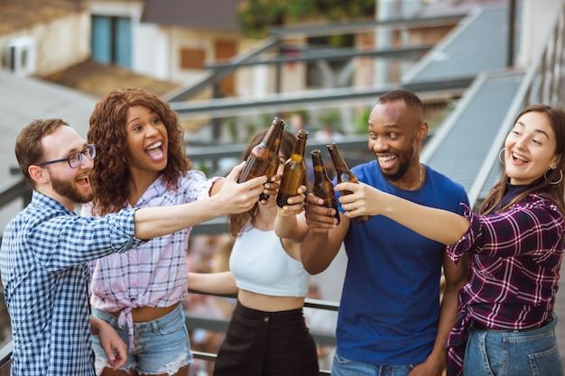 Gruppe von glücklichen freunden, die bierparty im sommertag haben. gemeinsam im freien ausruhen, feiern und entspannen, lachen. sommerlebensstil, freundschaftskonzept. Kostenlose Fotos
