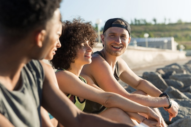 Gruppe von glücklichen jungen leuten in der sportbekleidung, die beim ausruhen sprechen Kostenlose Fotos