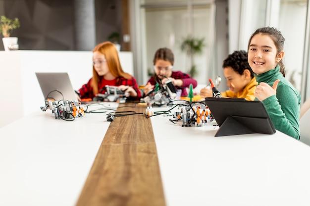 Gruppe von glücklichen kindern, die elektrisches spielzeug und roboter im klassenzimmer der robotik programmieren Premium Fotos