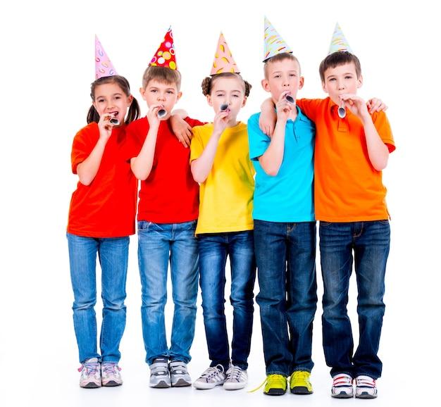 Gruppe von glücklichen kindern in farbigen t-shirts mit partygebläsen - lokalisiert auf einem weißen hintergrund Kostenlose Fotos