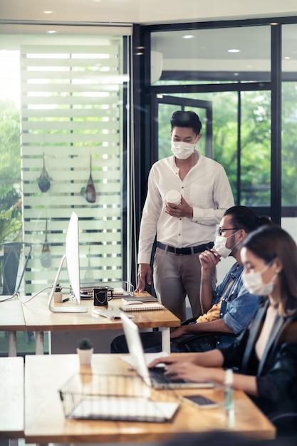 Gruppe von interracial geschäftsarbeiterteam tragen schützende gesichtsmaske im neuen normalen büro Premium Fotos