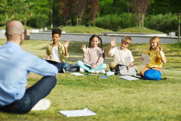 Gruppe von kindern, die hände heben, während sie in der reihe auf grünem gras sitzen und lehrerfragen in der klasse im freien beantworten, raum kopieren Premium Fotos