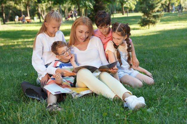 Gruppe von kleinen kindern, die ihren unterricht im freien im park mit lieblingslehrer genießen Premium Fotos