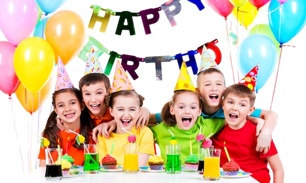 Gruppe von lachenden kindern, die spaß an der geburtstagsfeier haben - lokalisiert auf einem weiß. Kostenlose Fotos