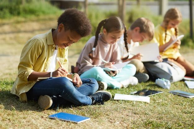 Gruppe von lächelnden kleinen kindern, die draußen studieren, sitzen in reihe auf grünem gras und schreiben in lehrbüchern, konzentrieren sich auf afroamerikanischen jungen im vordergrund, kopieren raum Premium Fotos