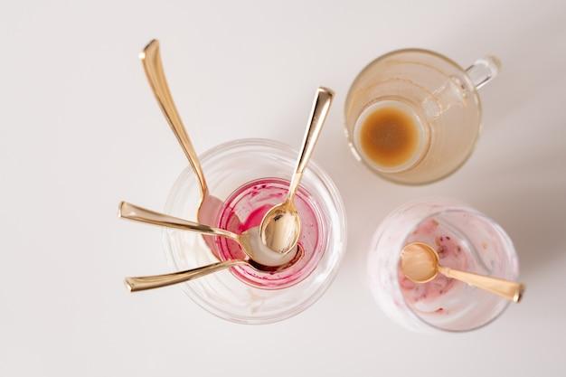 Gruppe von leeren ungewaschenen gläsern und teelöffeln auf küchentisch nach dem frühstück bestehend aus kaffee und joghurt mit hausgemachter marmelade Premium Fotos